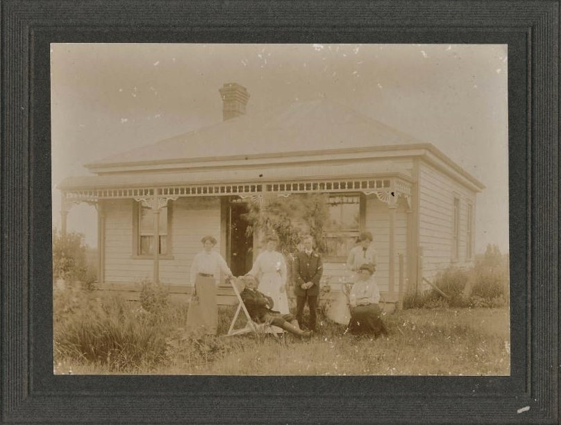 Mounted sepia photo of Monavale house in Cambridge NZ, with six people: three women standing and one sitting, and one man standing and one sitting in a deckchair.